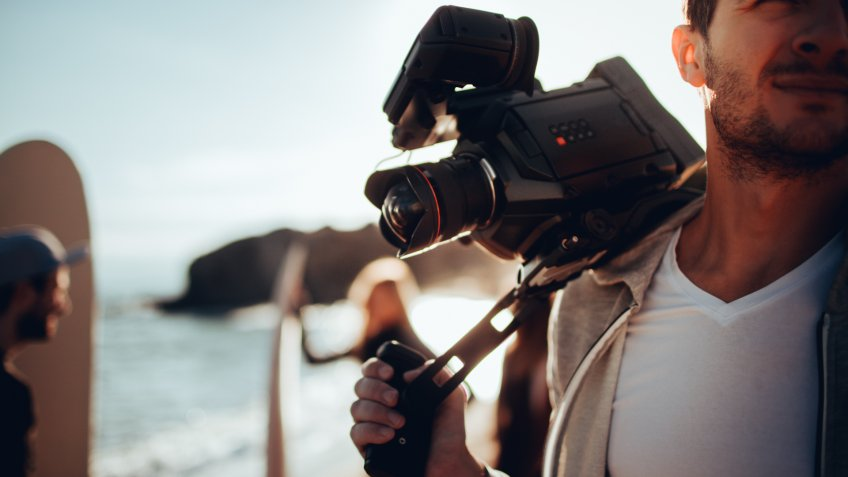 Young man holding video camera, having a photo shoot with his friends at the beach, while they are preparing to surf.