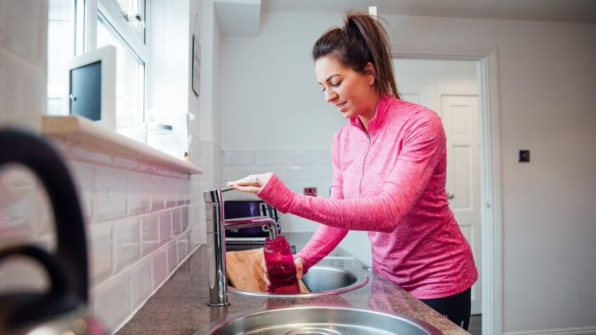 Mid adult woman is filling her reusable water bottle at home before she goes to the gym.