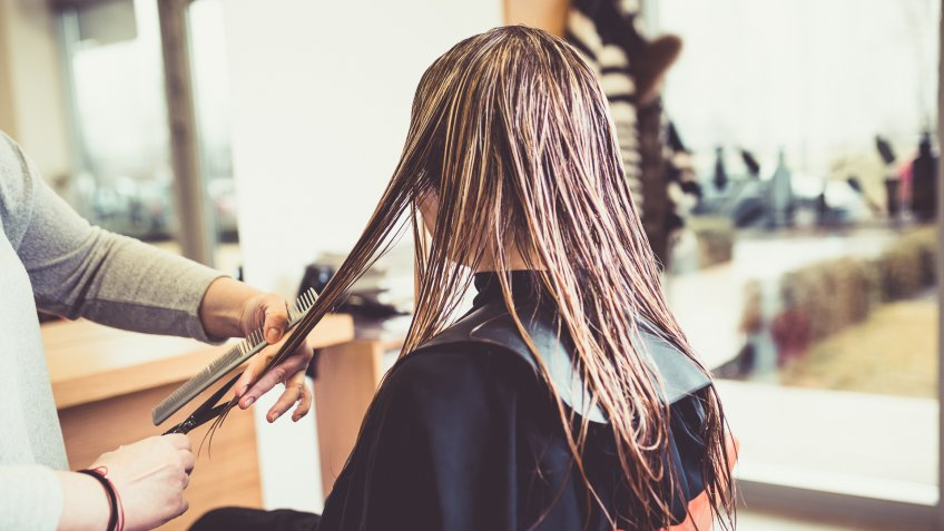 Close-up of a woman in hair salon getting her hair cut by the hairdresser.