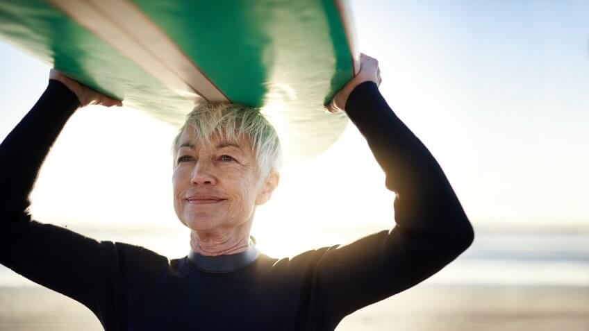 Cropped shot of a senior woman holding a surfboard on top of her head on her way to go surfing.