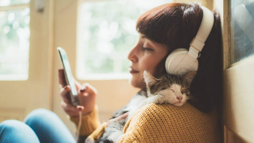Woman at home listening to music and cuddle her cat.