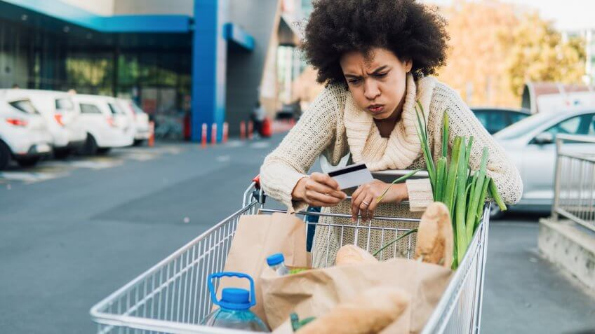 Woman pushing shopping cart and looking at credit card.