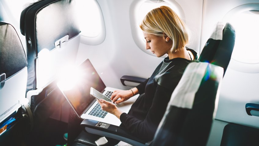woman on airplane with laptop