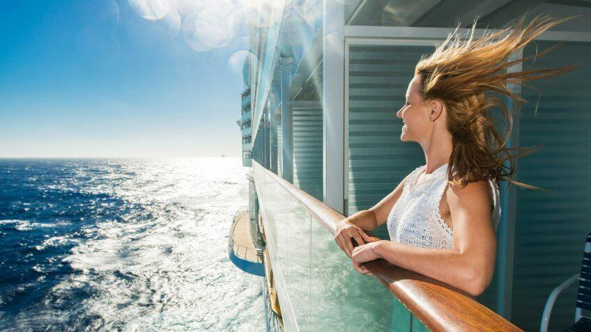 Smiling woman enjoying a day on a cruise ship and looking at view.