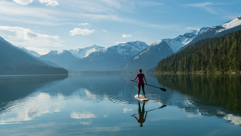 Woman stand up paddle boarding on a pristine mountain lake.