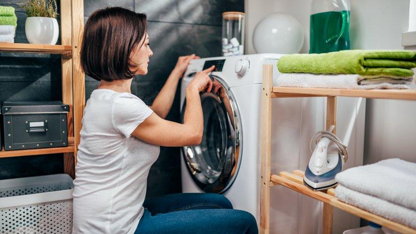 Woman wearing white shirt choosing program on washing machine in laundry room.