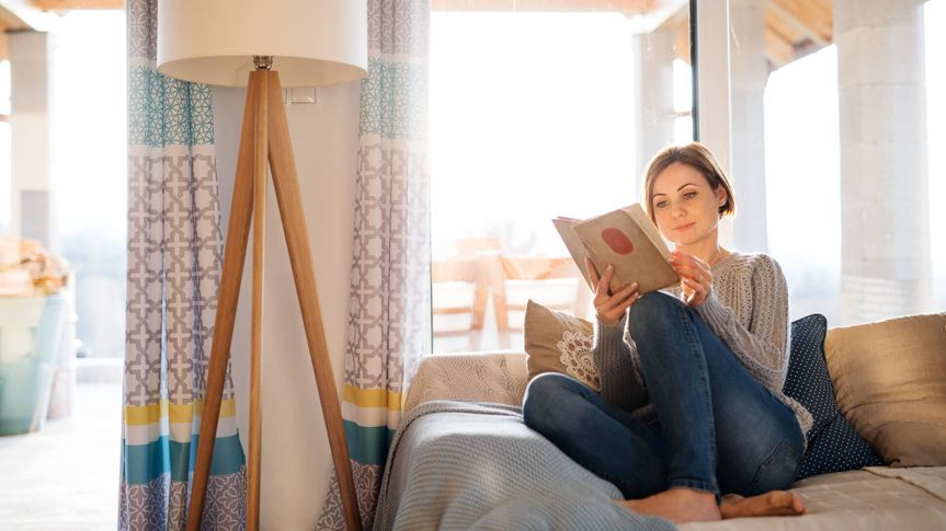 A young woman sitting barefoot indoors on a sofa at home, reading a book.