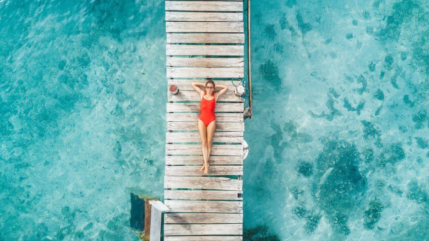 Aerial shot of womann relaxing in a water bungalow.