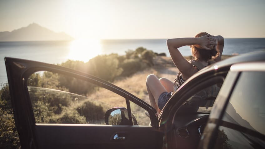 Woman relaxing on her car at the road trip.