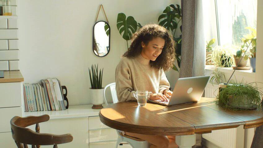 Beautiful young brunette woman sitting in cozy kitchen by a table and working on her laptop computer.