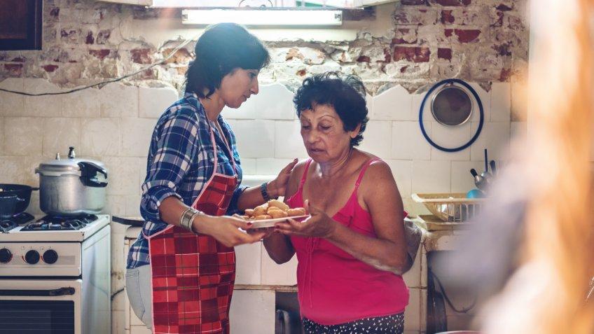 Multi-generation cuban family preparing dinner.