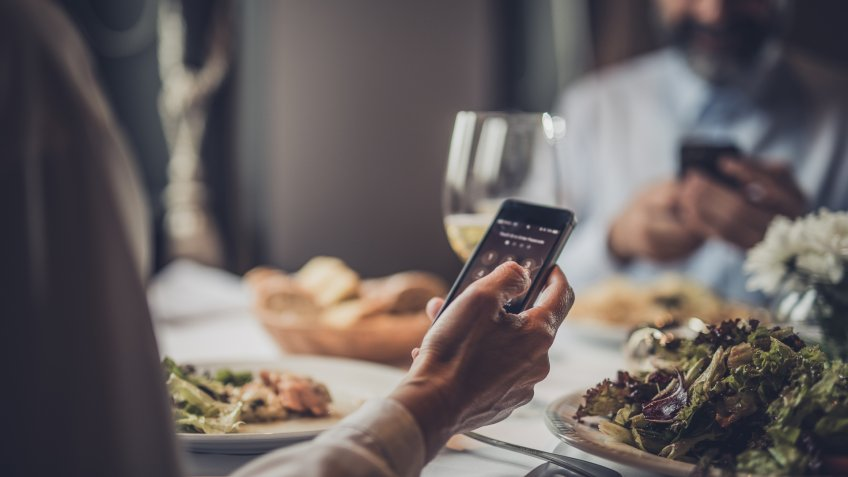 Close up of unrecognizable mature woman entering a PIN on her cell phone while being in a restaurant with her husband.