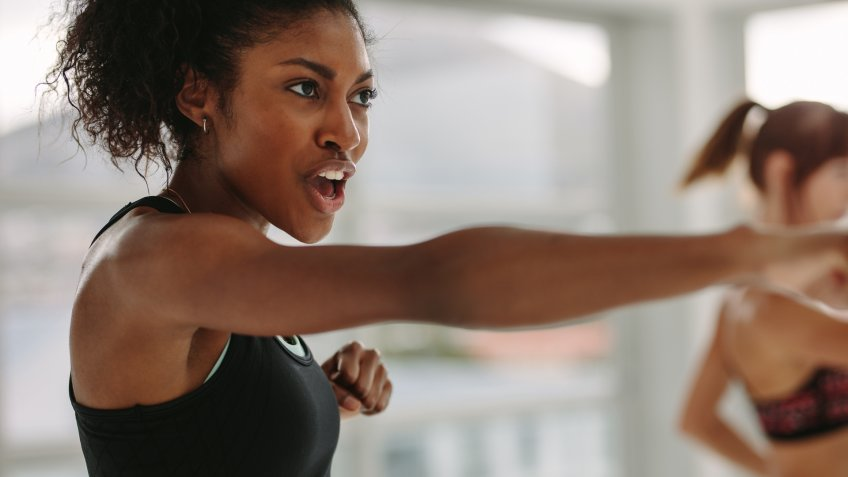 African young woman doing intense punching work out at the gym.