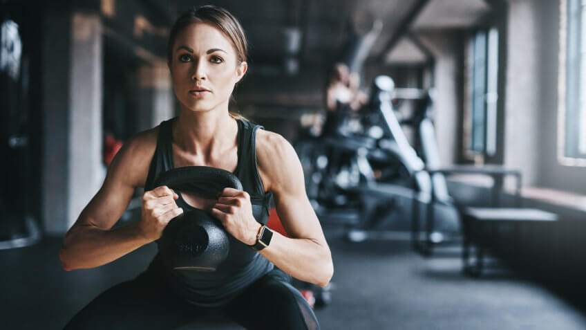 Cropped shot of an attractive young woman working out with a kettle bell in the gym.