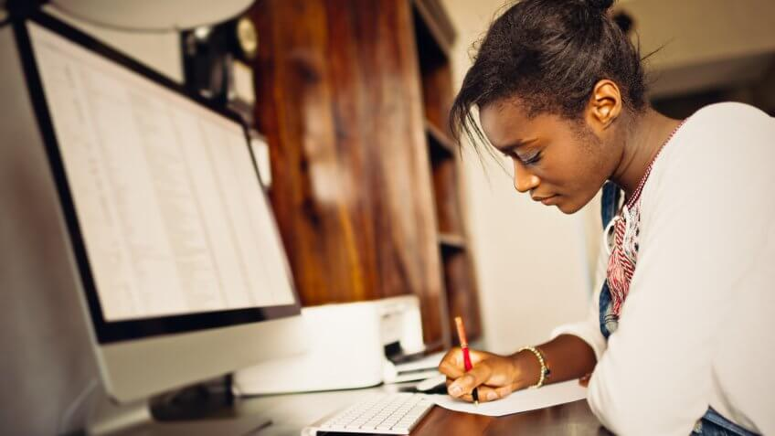 Young African woman studying home.