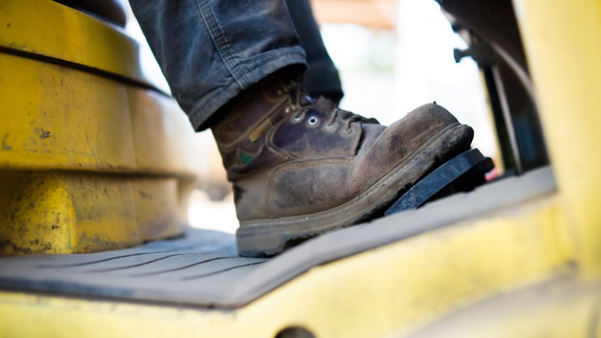 Close up of workboots of man driving forklift.