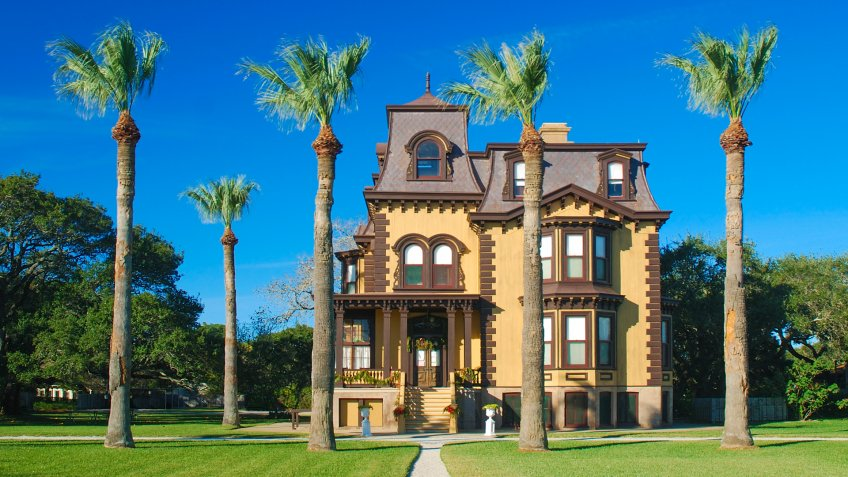 The mansion and palm trees look like a winter retreat.