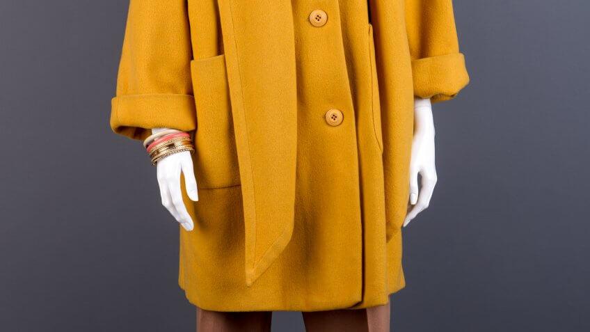 Female mannequin in yellow topcoat.