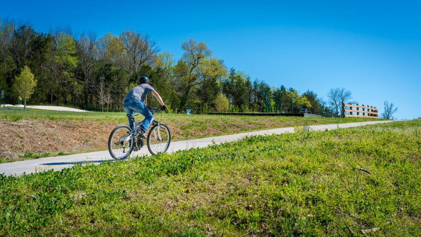 Young man biking on bike trail in Bella Vista, Northwest Arkansas - Image.