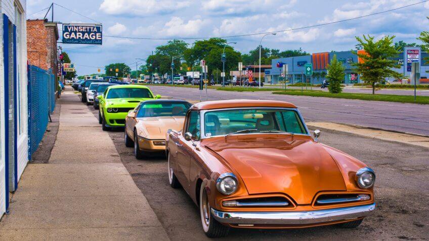 BERKLEY, MI/USA - AUGUST 16, 2018: Three classic cars in front of historic Vinsetta Garage, at Woodward Dream Cruise: 1953 Studebaker Commander Chevrolet C4 Corvette Dodge (SRT) Challenger Hellcat - Image.