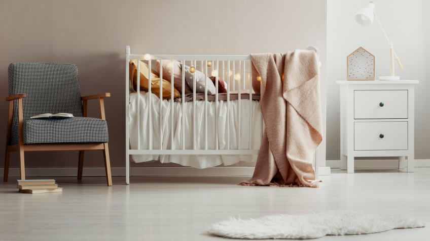Stylish vintage armchair next to white wooden crib with pastel pink blanket, pillows and cotton ball lights - Image.