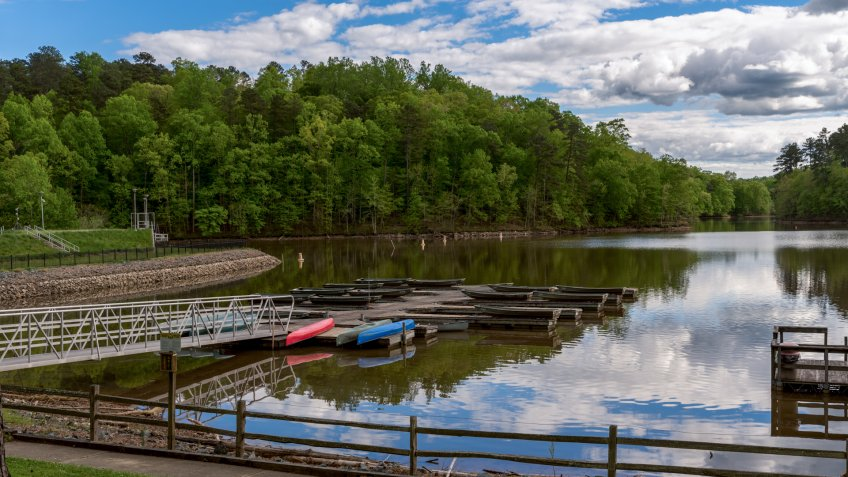Walkway leading to dock on a lake with upside down canoes with sky and clouds in the background - Image.