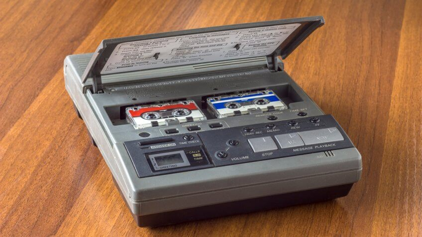 old vintage answering machine with two small tape cassettes on a wooden table surface - Image.