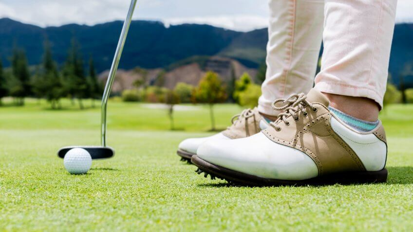 Golf player hitting a ball at the putting green - Image.