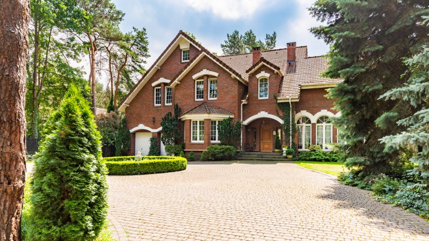 Large cobbled driveway in front of an impressive red brick English design mansion surrounded by old trees.