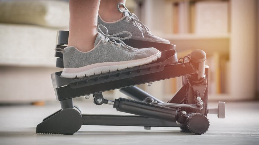 Woman doing exercises on stepper at home - Image.