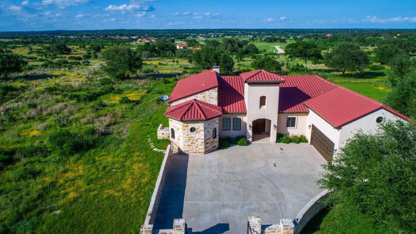 Aerial drone view above green landscape Luxury mansion home on vineyard winery open green Texas hill country landscape with Spanish architecture and large concrete courtyard.