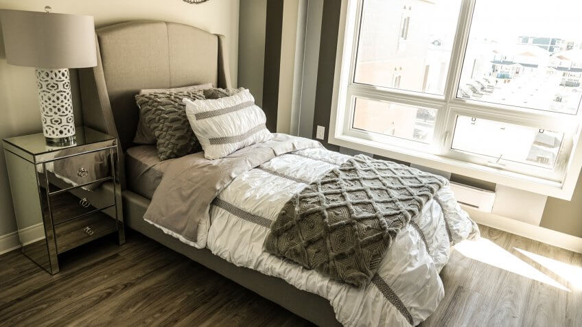 Neutral toned bedroom interior with twin size bed and open window with beautiful hardwood floors and silver mirrored side table.