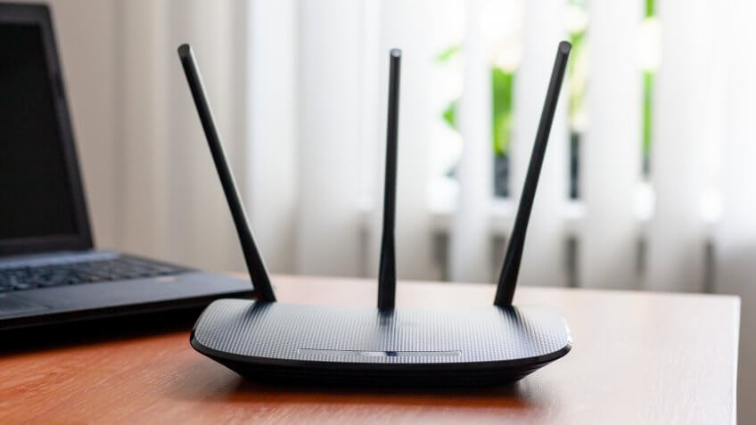 wireless wifi router and laptop at wooden table indoors.