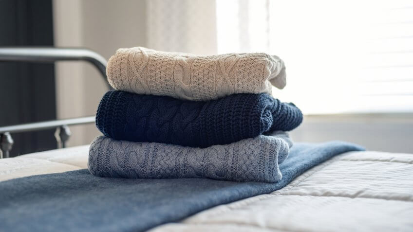 Stack of cable knit sweaters folded on the bed in morning light - Image.
