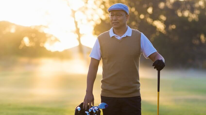 Full length of mature man standing at golf course.