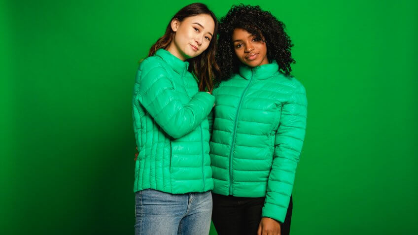Two female friends standing infront of a green background in a studio.