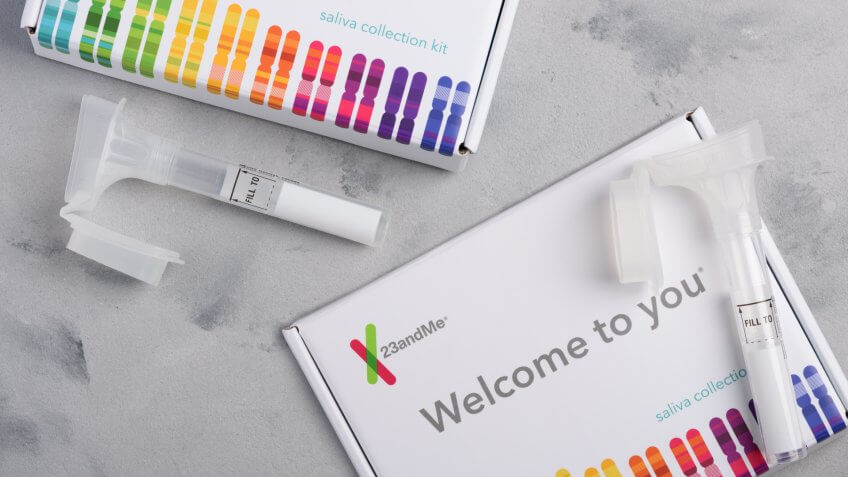 Kiev, Ukraine - 17 October 2018: 23andMe personal genetic test saliva collection kit, with tube and box on table overhead view.