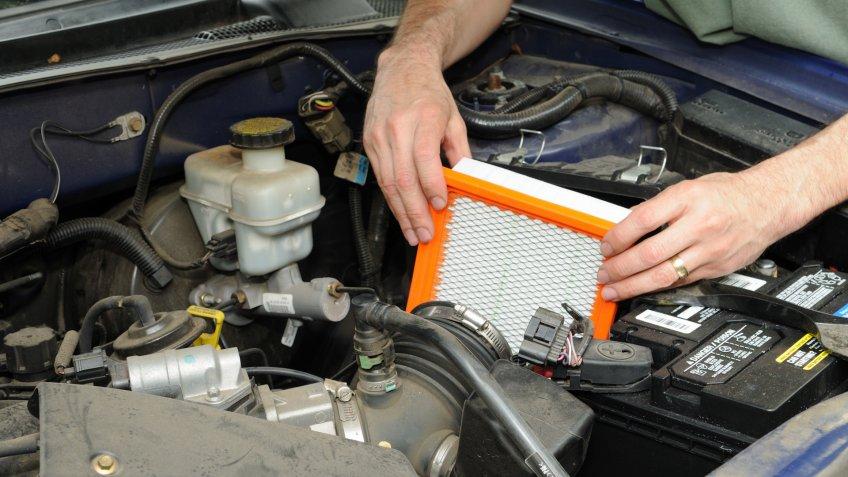 Man replacing an automotive air filter.
