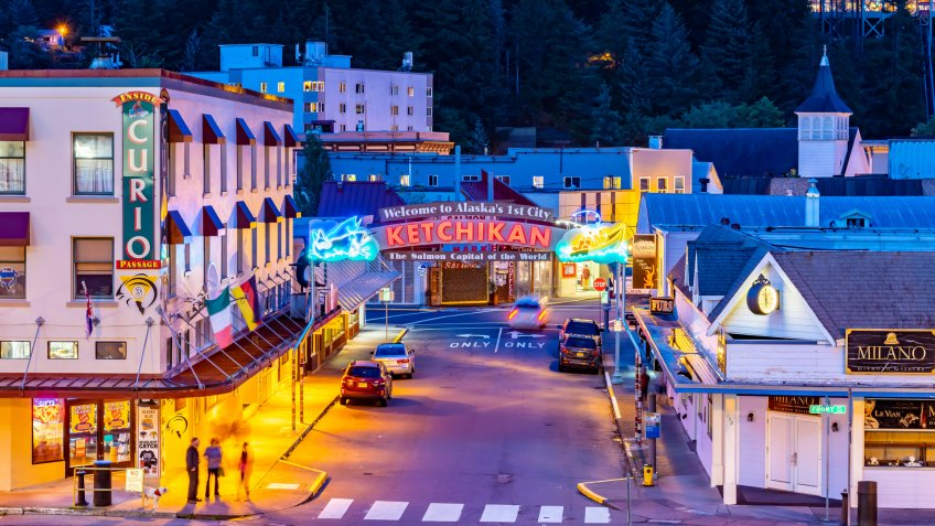Ketchikan, Alaska - September 30 2017: Night aerial/drone view on Front Street, downtown with Welcome to Alaska 1st City neon sign, buildings, vehicles driving and parked, people walking and standing.