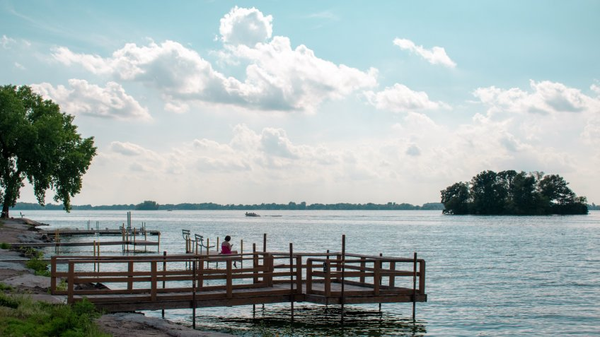 A woman sitting at the end of the pier at waterworks park in beaver dam Wisconsin - Image.