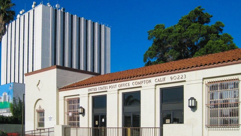 Compton, California USA - June 9, 2017: historic 1935 WPA United States Post Office exterior, 101 S Willowbrook Ave, Spanish Revival, near Civic Plaza, Los Angeles Superior Courthouse in background.