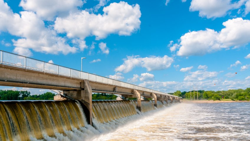The waters of the Mississippi River flow briskly over the Coon Rapids Dam just outside of Minneapolis, Minnesota on a sunny summer day with blue skies and white clouds.