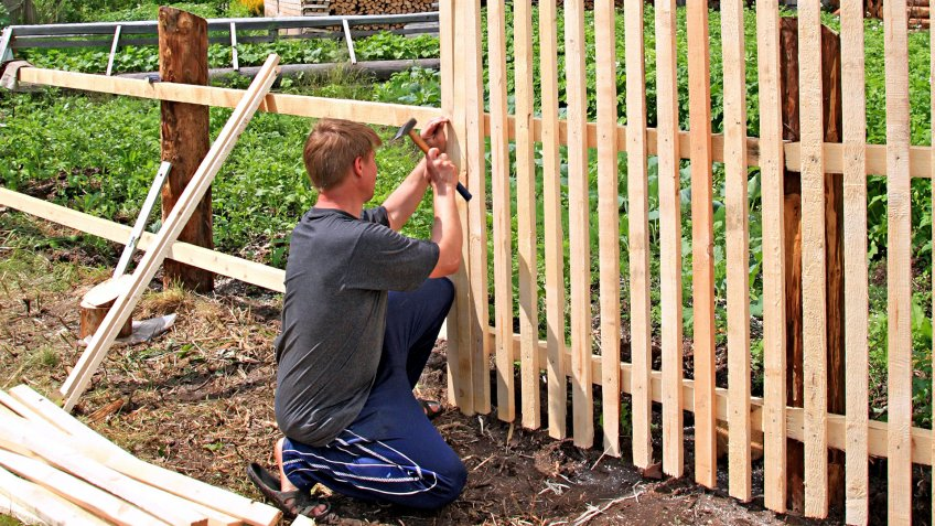 man builds fence - Image.