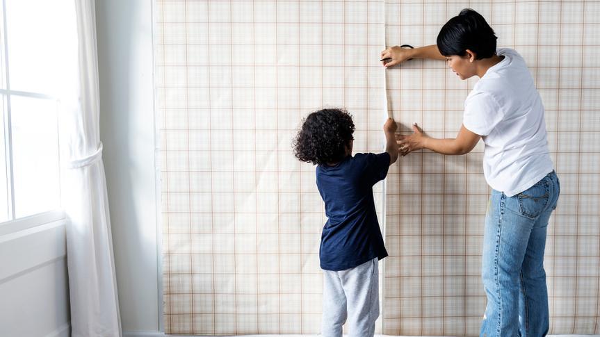 Kid helping mom install wallpaper - Image.