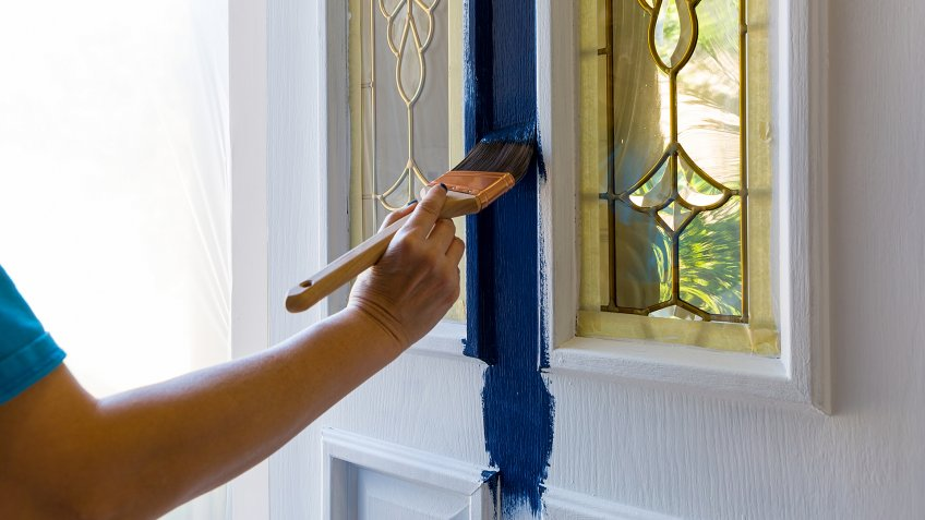 Female hand holding Brush painting house front door with blue paint at home do it yourself project.