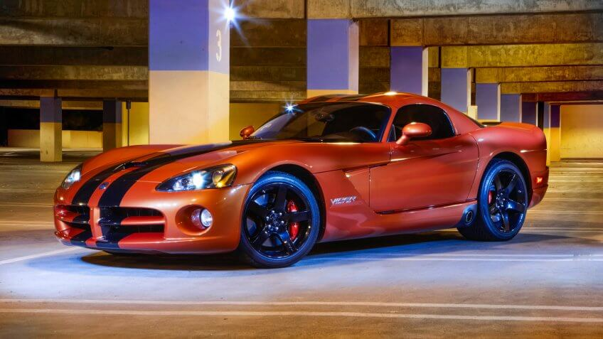 """Thousand Oaks, California USA - September 11,2011: Dodge Viper SRT10 orange with black stripes, profile low angle shot, photographed in the a parking garage with flashes and spot lights."