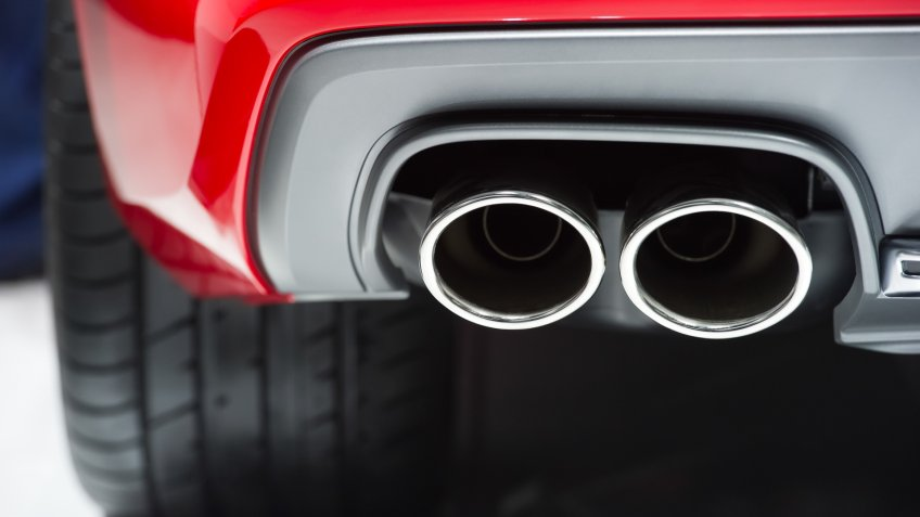 Chrome exhaust pipe of red powerful sport car bumper.