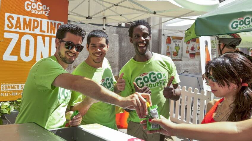 NEW YORK - AUGUST 04: Sales representatives of GoGo Squeez give juice samples at picnic area sponsored by Whole Foods during Summer Streets sponsored by DOT in Manhattan on Aug 4, 2012 in NYC - Image.