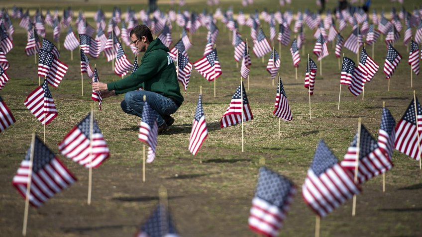 Iraq War Veteran-touches American Flag at US Veteran Suicide Epidemic event