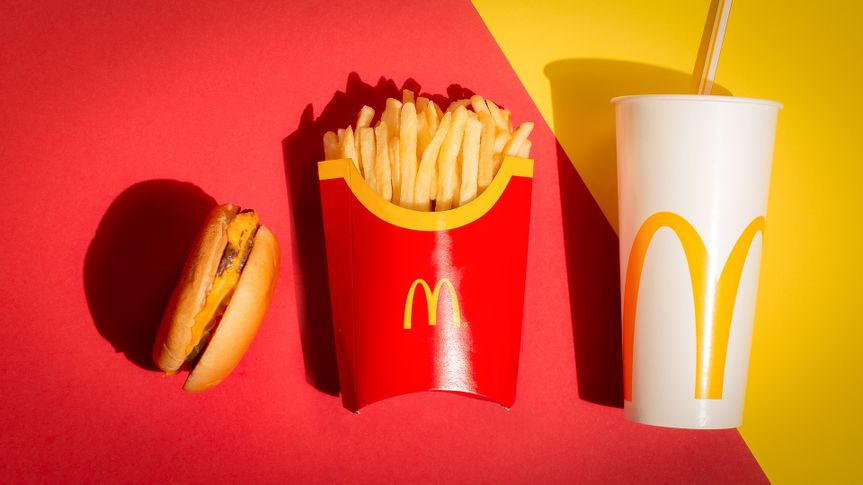 McDonalds cheeseburger fries and drink on red and yellow backgro